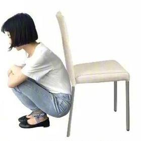膝关节康复病人可选择在两膝之间夹健身球练习靠墙半蹲.图片